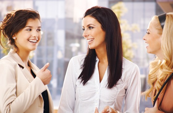 Attractive female friends talking, smiling outdoors.